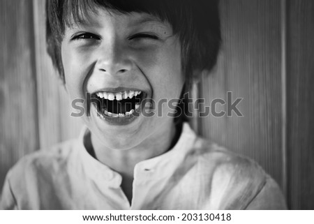 Black and white portrait of a happy cute little boy laughing