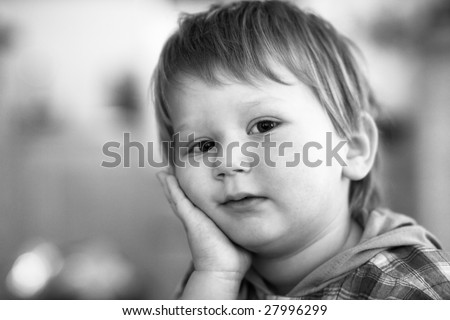 Black and white portrait of a little blond boy; blurred background; some grain