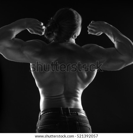 black-and-white portrait of a naked torso back male bodybuilder athlete in the studio on a black background