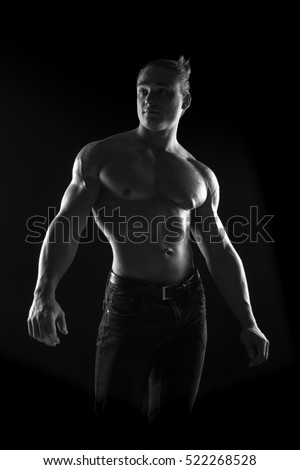black-and-white portrait of a naked torso male bodybuilder athlete in the studio on a black background