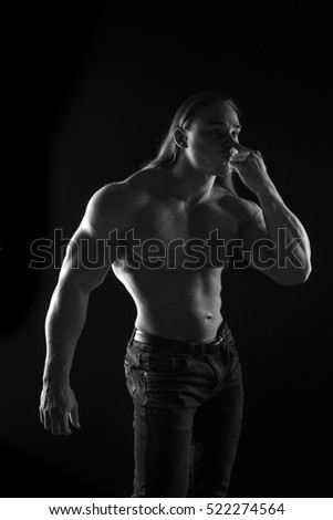 black-and-white portrait of a naked torso male bodybuilder athlete with long blond hair in studio on a black background
