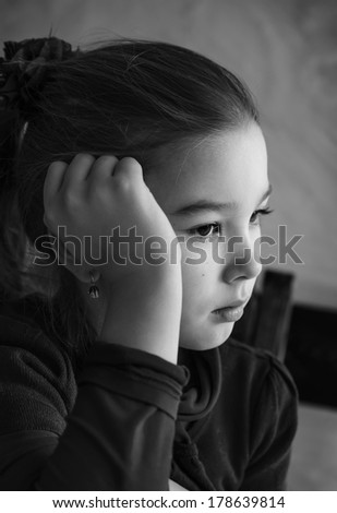 Black and white portrait of a pensive little girl. - stock photo