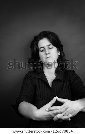 Black and white portrait of a sad and stressed hispanic woman sitting on the floor with space for text - stock photo