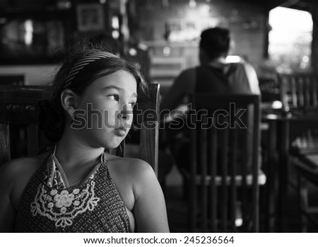 Black and white portrait of a sad little girl in cafe  - stock photo