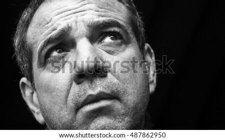 Black and white portrait of a sad man looking up.