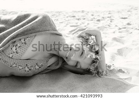 Black and white portrait of a senior beautiful woman laying down on a sandy beach shore, looking and smiling at camera on holiday, nature outdoors. Travel lifestyle and healthy living, sunny exterior.