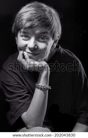 black and white portrait of a smiling male teenager with black background. - stock photo