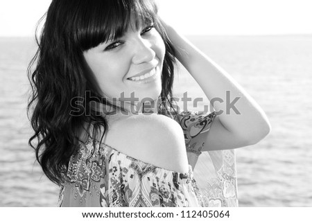 Black and white portrait of a smiling woman enjoying summer evening, vertical shot - stock photo