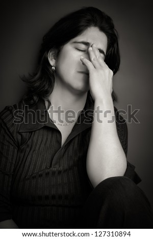 Black and white portrait of a stressed  woman suffering a headache - stock photo