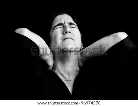 Black and white portrait of a stressed woman suffering from neck pain on a black background with space for text - stock photo