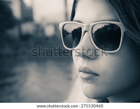 Black and white portrait of a teenage girl in colorful sunglasses close up - stock photo