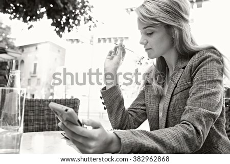 Black and white portrait of a thoughtful young business woman using a smart phone, working in a coffee shop terrace in a city, outdoors. Professional businesswoman drinking water, sunny exterior. - stock photo