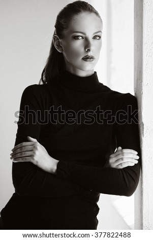 Black and white portrait of a woman with crossed arms. - stock photo