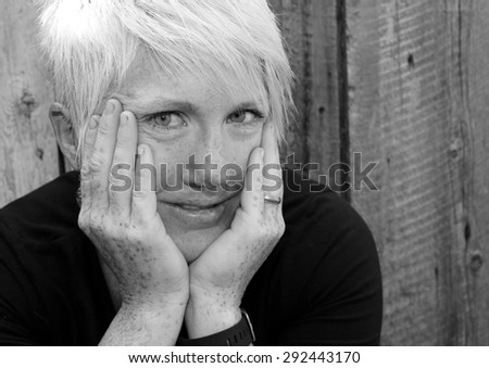 Black and White portrait of a woman with hands on her face.