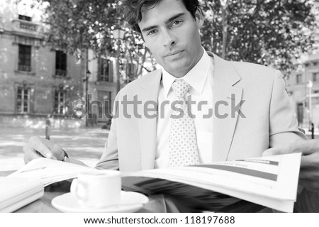 Black and white portrait of a young attractive businessman reading the newspaper while sitting at a coffee shop terrace table, outdoors, in a classic city square with trees. - stock photo