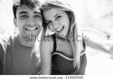 Black and white portrait of a young attractive tourist couple using a smartphone to take a selfie picture of themselves on holiday while visiting a touristic destination city, having fun outdoors. - stock photo
