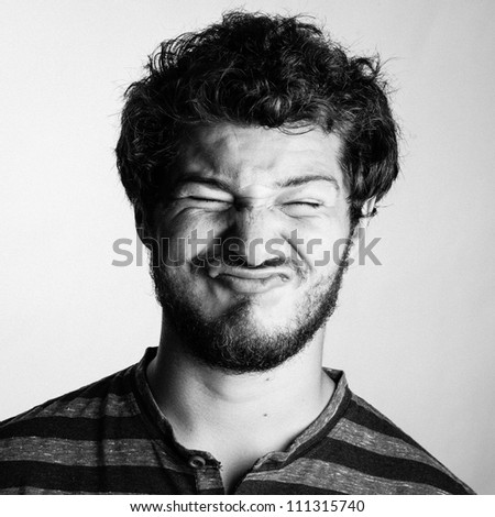 Black and White Portrait of a Young College boy wth his eyes tightly shut - stock photo