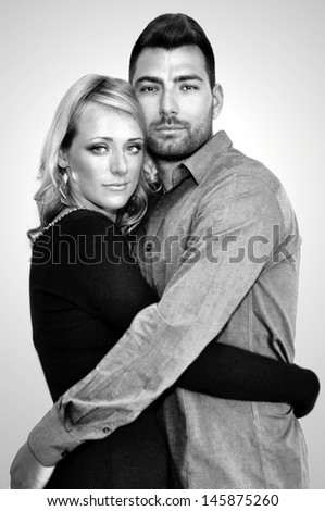 Black and white portrait of a young couple hugging. - stock photo
