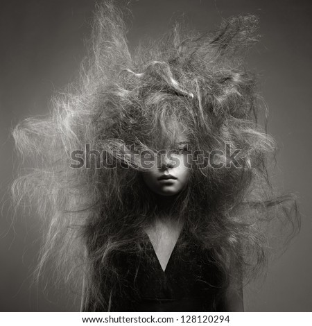 Black and white portrait of a young girl with a volume fashionable hairstyle - stock photo