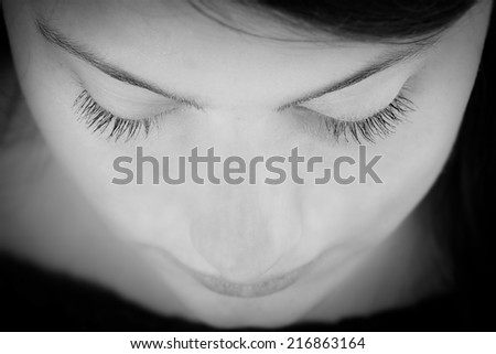 Black and white portrait of a young woman, teenage girl, contemplating, looking down with her eyes closed - stock photo