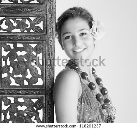 Black and white portrait of an attractive young woman wearing an exotic outfit and jewelry and leaning on a carved wood screen panel while on vacations at a health spa, smiling.