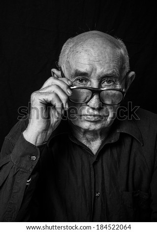 Black and White Portrait of an elderly man with a serious expression. - stock photo
