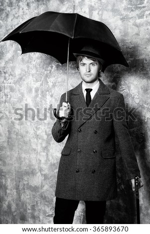 Black-and-white portrait of an elegant young man wearing classic hat and a coat standing with his black umbrella. Beauty, fashion. - stock photo