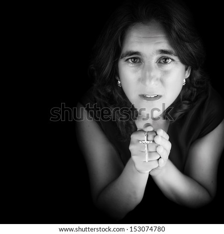 Black and white portrait of an hispanic woman praying and holding a small crucifix (isolated on black with copy space)