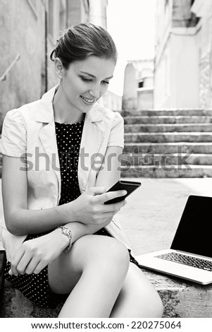 Black and white portrait of attractive young business woman using smartphone and laptop computer while sitting on a stone steps in a classic city, smiling outdoors. Professional people and technology.