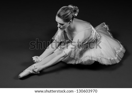 Black and white portrait of ballerina tying up pointe shoes - stock photo