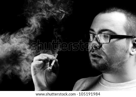 Black and white portrait of bearded man smoking cigarette - stock photo