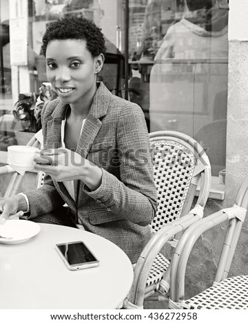 Black and white portrait of beautiful african american business woman sitting drinking coffee with smart phone, looking smiling, city outdoors. Professional black businesswoman lifestyle, exterior.