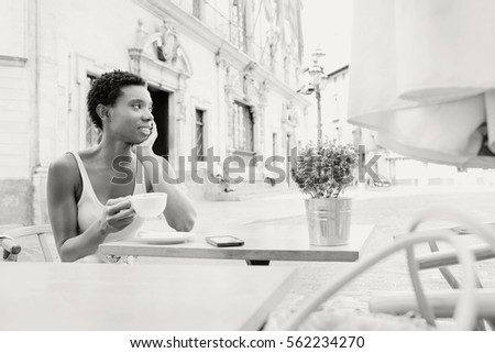 Black and white portrait of beautiful african american professional woman sitting in coffee shop terrace drinking, smiling outdoors. Black tourist woman in city destination with smart phone, space.