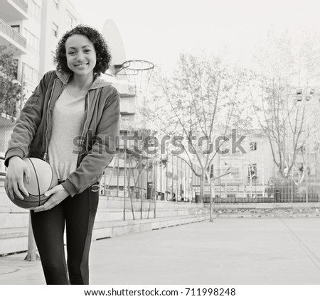 Black and white portrait of beautiful african american teenager student girl in basketball court holding basket ball, looking smiling, university sports. Black female fitness and active lifestyle.