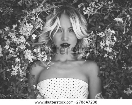Black and white portrait of beautiful lady in the flowered garden - stock photo