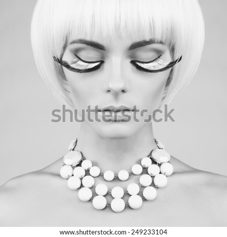 Black and white portrait of beautiful lady with eyelashes and necklace - stock photo
