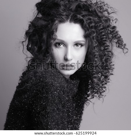 Black and white portrait of beautiful sexy young lady with curly disheveled hair in black sweater fashion studio photo