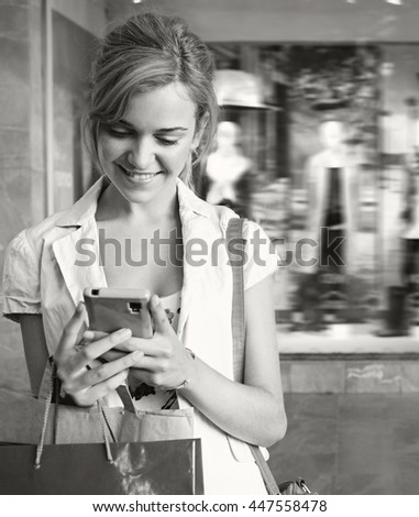 Black and white portrait of beautiful smiling young tourist woman using a smart phone, shopping in a shopping mall with fashion store window in background, technology and consumer lifestyle, outdoors. - stock photo
