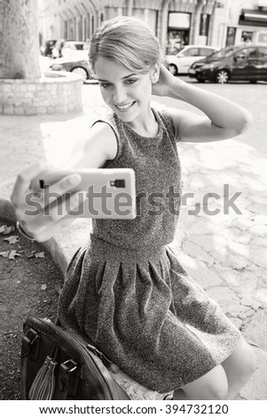 Black and white portrait of beautiful tourist young woman using a smart phone networking in city with classic buildings outdoors. Confident aspirational lifestyle, smiling with technology, exterior.