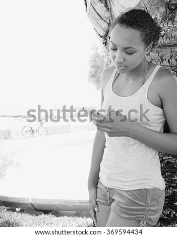 Black and white portrait of beautiful young african american woman holding using a smartphone, networking relaxing on beach park, outdoors. Sporty lifestyle using technology, teenager exterior. - stock photo