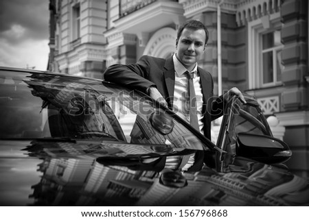 Black and white portrait of businessman standing near car - stock photo