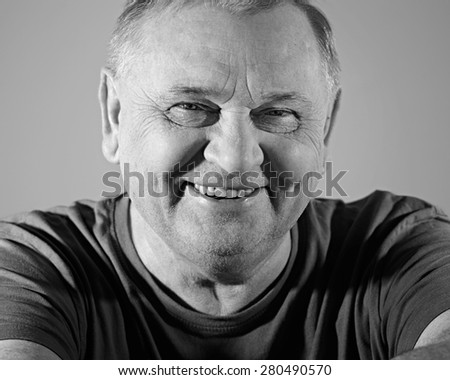 Black and white portrait of cheerful aged man in t-shirt smiling with dimples - stock photo