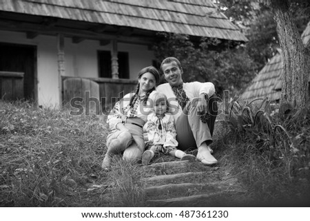Black and white portrait of cheerful family dressed in embroidered clothes