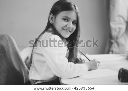 Black and white portrait of cheerful girl doing homework - stock photo