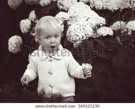 Black and white portrait of cute adorable surprised crying screaming baby boy girl child standing among flowers, lifestyle, happy childhood concept, retro vintage style - stock photo