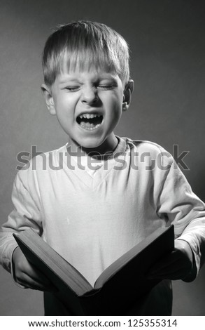 black and white portrait of cute little boy with book laughs - stock photo