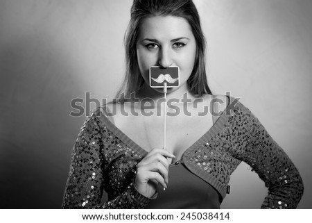 Black and white portrait of cute woman holding decorative mustache at mouth - stock photo