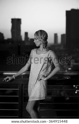Black and white portrait of elegant blonde woman posing in cocktail wear on balcony with the city behind her