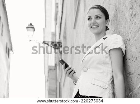 Black and white portrait of elegant business woman in a classic city with textured stone buildings and walls, holding a high technology smartphone in her hand, smiling outdoors. People and technology. - stock photo