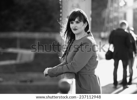 Black and white portrait of elegant woman standing on bridge at windy day - stock photo